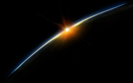 sun rising over the earth from space